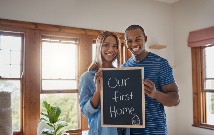 Shot of a couple holding up a blackboard as they move into their new house