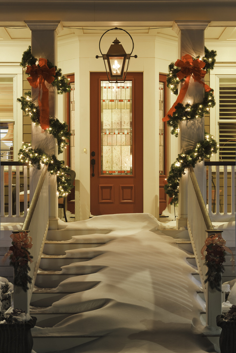 Inviting Christmas home doorway with snowy porch at night